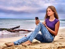 Muchacha con el teléfono móvil que se sienta en la arena cerca del mar Fotografía de archivo libre de regalías