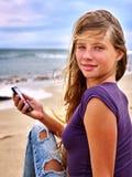 Muchacha con el teléfono móvil que se sienta en la arena cerca del mar Imagenes de archivo
