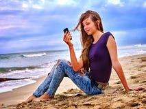 Muchacha con el teléfono móvil que se sienta en la arena cerca del mar Foto de archivo libre de regalías