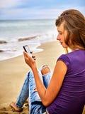 Muchacha con el teléfono móvil que se sienta en la arena cerca del mar Imagen de archivo