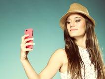 Muchacha con el teléfono móvil que toma la foto de sí misma Fotos de archivo