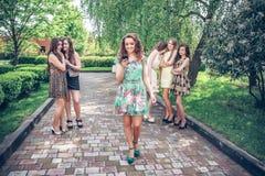 Muchacha con el teléfono móvil y grupo de envidiar a muchachas Foto de archivo libre de regalías
