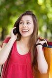 Muchacha con el teléfono móvil y los bolsos de compras Foto de archivo
