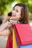 Muchacha con el teléfono móvil y los bolsos de compras Imagenes de archivo