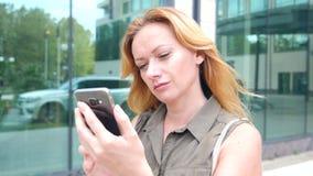 Muchacha con el teléfono paseos en un día soleado caliente en una ciudad moderna fondo de rascacielos 4K Cámara lenta almacen de video