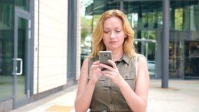 Muchacha con el teléfono paseos en un día soleado caliente en una ciudad moderna fondo de rascacielos 4K Cámara lenta metrajes