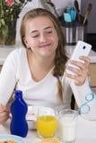 Muchacha con el teléfono que desayuna en cocina Fotografía de archivo