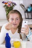 Muchacha con el teléfono que desayuna en cocina Fotografía de archivo libre de regalías