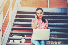 Muchacha con el teléfono que habla del ordenador portátil Imágenes de archivo libres de regalías