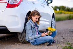 Muchacha con el teléfono que se sienta en la tierra al lado del coche Imagenes de archivo