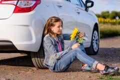 Muchacha con el teléfono que se sienta en la tierra al lado del coche Imagen de archivo libre de regalías