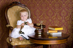 Muchacha con el teléfono que se sienta en una silla vieja Foto de archivo