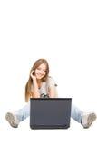 Muchacha con el teléfono y la computadora portátil Fotografía de archivo libre de regalías
