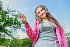 muchacha con el teléfono y los auriculares Imagen de archivo