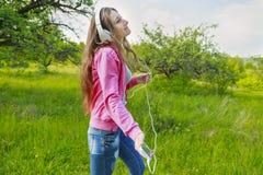 muchacha con el teléfono y los auriculares Imágenes de archivo libres de regalías