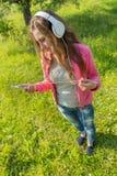 muchacha con el teléfono y los auriculares Fotografía de archivo libre de regalías