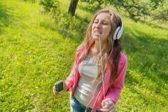 muchacha con el teléfono y los auriculares Fotografía de archivo