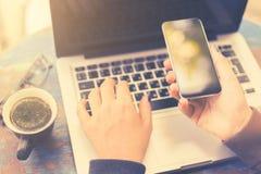 Muchacha con el teléfono celular, el ordenador portátil y la taza de café en blanco Imagenes de archivo