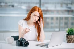 Muchacha con el termómetro que se sienta en el ordenador portátil y que mira la red qué hacer Foto de archivo libre de regalías