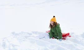 Muchacha con el trineo que se sienta en nieve Foto de archivo