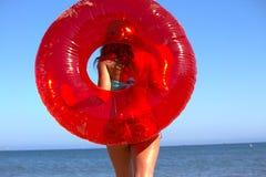Muchacha con el tubo interno rojo de la blanco en la playa Fotos de archivo