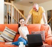 Muchacha con el varón adulto con el ordenador portátil Imagen de archivo libre de regalías