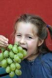 Muchacha con el vestido que come las uvas blancas Imágenes de archivo libres de regalías