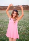 Muchacha con el vestido rosado que celebra algo en un campo por completo de la Florida Imágenes de archivo libres de regalías