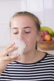 Muchacha con el vidrio de leche en cocina Imágenes de archivo libres de regalías