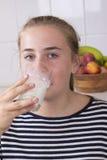 Muchacha con el vidrio de leche en cocina Fotografía de archivo libre de regalías