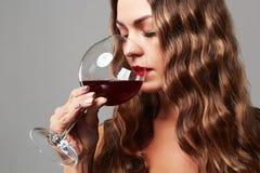 Muchacha con el vidrio de vino rojo Mujer rubia hermosa que bebe el vino rojo foto de archivo