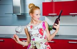 Muchacha con el vidrio y la botella de vino en cocina Imagen de archivo libre de regalías