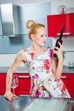 Muchacha con el vidrio y la botella de vino en cocina Fotos de archivo