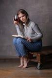 Muchacha con el vino Fondo gris Imagen de archivo