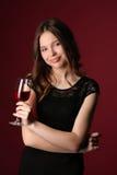 Muchacha con el vino y los brazos cruzados Cierre para arriba Fondo rojo oscuro Imagen de archivo libre de regalías