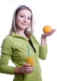 Muchacha con el zumo de naranja y la naranja en su mano Imagen de archivo