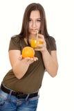 Muchacha con el zumo de naranja y la naranja en su mano Imagenes de archivo