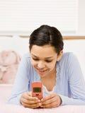 Muchacha con envío de mensajes de texto de las paréntesis con el teléfono celular Fotos de archivo
