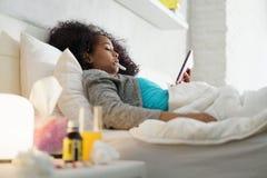 Muchacha con fiebre usando el termómetro y la tableta en cama Fotos de archivo