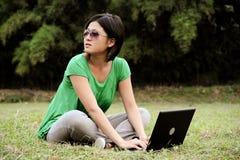 Muchacha con gafas de sol y un ordenador fotografía de archivo