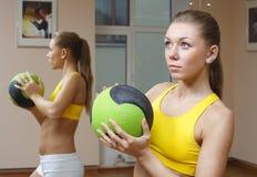 Muchacha con gimnasia de la aptitud del fondo del espejo de la bola Imagenes de archivo