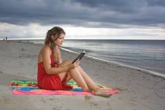 Muchacha con la alineada roja que lee un libro en la playa Imagenes de archivo