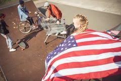 Muchacha con la bandera americana que mira a los amigos que se divierten en el parque del monopatín Fotos de archivo libres de regalías