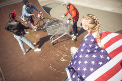 Muchacha con la bandera americana que mira a los amigos que se divierten en el parque del monopatín Fotografía de archivo