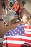 Muchacha con la bandera americana que mira a los amigos que se divierten en el parque del monopatín Imágenes de archivo libres de regalías