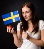 Muchacha con la bandera sueca que sostiene una manzana y un x28; marie& x29 de Ingrid; Imagen de archivo libre de regalías
