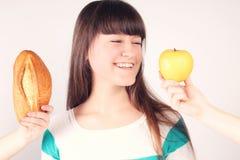 Muchacha con la barra de pan y la manzana Imagen de archivo