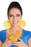 Muchacha con la bebida anaranjada y el fondo anaranjado del blanco de los pendientes de la rebanada Fotos de archivo