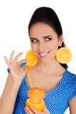 Muchacha con la bebida anaranjada y el fondo anaranjado del blanco de los pendientes de la rebanada Fotos de archivo libres de regalías