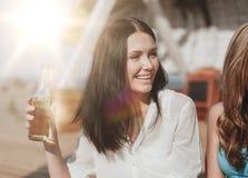 Muchacha con la bebida y amigos en la playa Imagenes de archivo